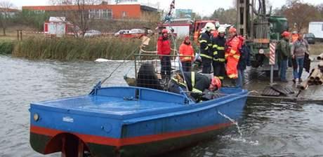 Hasiči vytahují člun potopený na Nových Mlýnech.