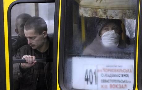 Žena s ochrannou rouškou v autobuse hromadné dopravy v Kijevě na Ukrajině. (2. listopadu 2009)