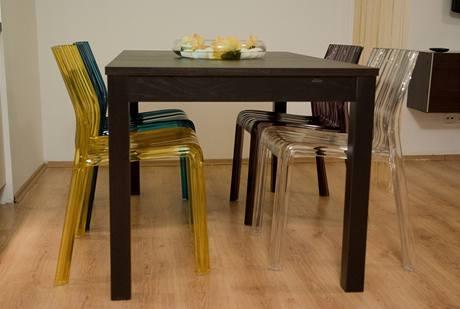 U dřevěného stolu jsou čtyři plastové židle vbarvách, které se v interiéru opakují i na textilu