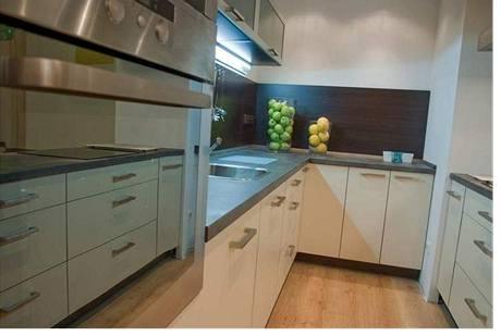Světlou kuchyni doplňuje tmavý obklad za pracovní deskou