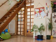 Vmístnosti je dřevěné schodiště, barevně sním ladily i dveře