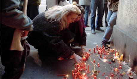 Mladá žena umisťuje svíčku na místě kde došlo k násilí na demonstrantech z Albertova v podloubí na Národní třídě 19. listopadu 1989.