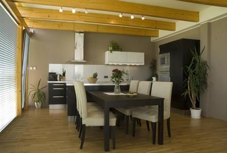 Majitelé domu si do velkého světlého prostoru vybrali kuchyňskou linku v dýze wengé a jídelní stůl ve