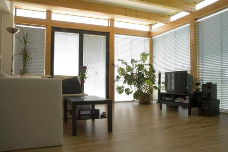 Obývací pokoj lemuje masivní dřevěná rámová konstrukce, vymezující pevně zasklené plochy