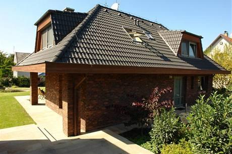Charakteristickým znakem domů architekta Jiřího Houši je přesahující valbová střecha s výraznými lichoběžníkovými vikýři a obezdívka z režných cihel