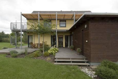 Dům se sedlovou střechou má dvě nízké přízemní přístavby, obě obložené dřevem