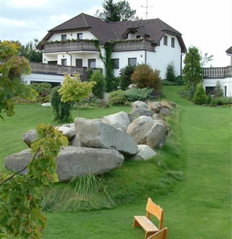 Oba domy opticky odděluje velkolepé suťové pole z obřích i menších kamenů, jež se valí zahradou směrem dolů.