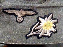 Čepice jednotky Alpská protěž se svým znakem.