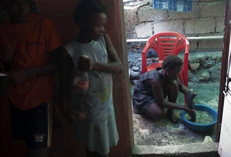 Patnáctiletá Saintia Pierreová (u mísy s prádlem)  je jednou ze zhruba 170 000 dětských sloužících na Haiti