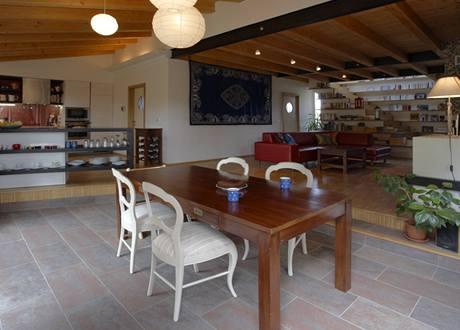 V popředí jídelna, vlevo kuchyň oddělená servírovacím barem, vpravo obytný prostor se schody do patra