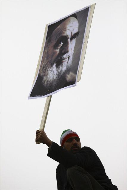 Demonstrant třímá v ruce portrét ajatolláha Rúholláha Chomejního