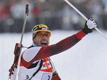 Christoph Sumann oslavuje s rakouskou vlajkou poté, co do cíle přivezl štafetu na prvním místě