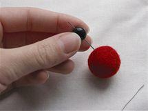 Vyberte vhodný korálek podle vlastního vkusu a přidejte na drátek nad plstěnku.