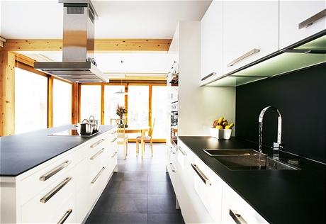 Dvě stěny kuchyně jsou zcela prosklené, v létě se jídelní část stane takřka součástí zahrady