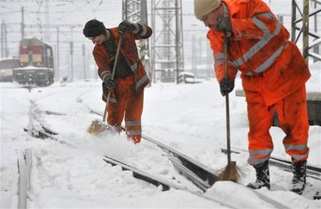 Pracovníci Českých drah odklízí sníh z kolejí na pardubickém hlavním nádraží.