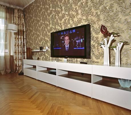 Výrazná prvek v bytě představují textilie a tapety, které dělají byt útulnější