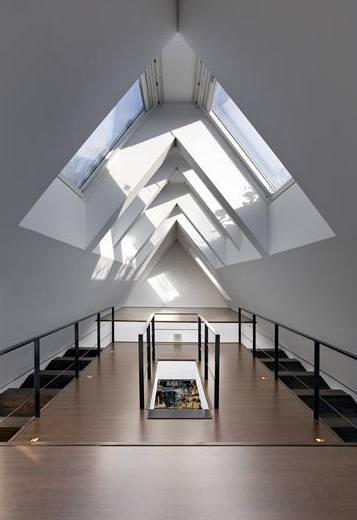 Halu v podkroví prosvětlují dvě řady střešních oken umístěné v rovnoběžných liniích nad sebou