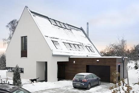 Přístavba garáže svým dřevěným obložením příjemně kontrastuje s bílou fasádou domu