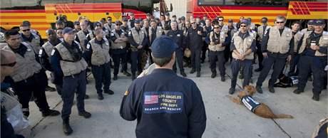 Američtí hasiči se speciálně cvičenými psy čekají na odlet na Haiti. (14. ledna 2010)