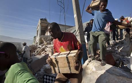Haiťané vynášejí zboží z jedné ze zhroucených budov