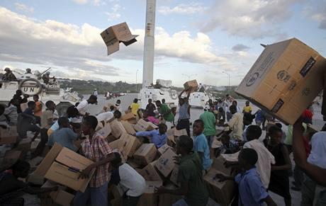 Haiťané odnášejí krabice z místa, kde OSN rozdávala potravinovou pomoc