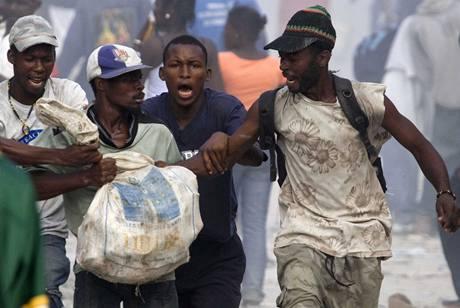Na snímku pořízeném agenturou Xinhua se Haiťané perou o věci získané při rabování
