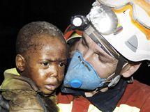 Španělský záchranář nese malého chlapce, kterého vytáhli živého z trosek pobořeného domu. (15. ledna 2010)