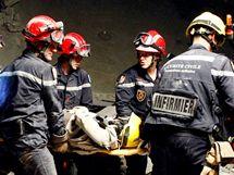 Francouzští a španělští záchranáři vynášejí šedesátipětiletou Američanku, která přežila více než 50 hodin uvězněná v troskách hotelu. (15. ledna 2010)