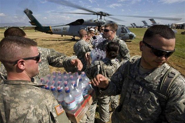 Ameri�tí vojáci na Haiti vykládají pomoc z helikoptéry