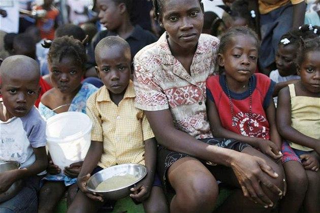 �ena s malými d�tmi �eká na p�íd�l potravin v provizorním stanovém m�ste�ku na p�edm�stí Port-au-Prince. (29. ledna 2010)