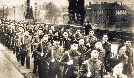 Milicionáři pochodují po Karlově mostě na přehlídku na Staroměstském náměstí v Praze v roce 1948.