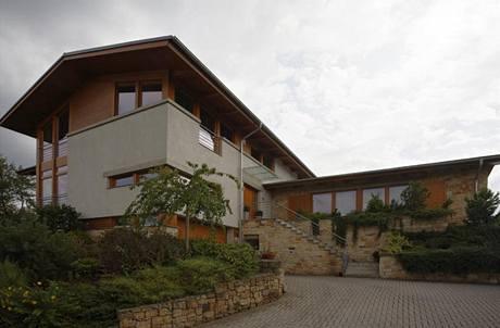 K dvoupodlažní hlavní obytné části s nízkými sedlovými střechami přiléhá přízemní bazén - vpravo