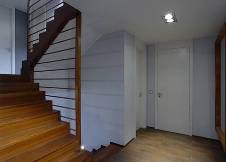 Centrální schodiště obložené tropickým dřevem lemuje atypické zábradlí konstruované ze dřeva a horizontálních měděných trubek