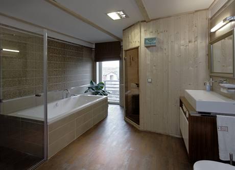 Rodinná koupelna svestavnou saunou je osvětlena velkým francouzským oknem a funguje pro celou rodinu jako další obytná místnost