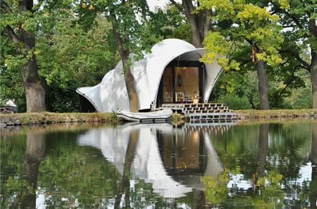 Chata s plátěnou střechou na břehu rybníka