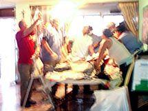 Operace nohy zraněného muže na jídelním stole v kuchyni.