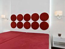 Stěna za lůžkem s vtipnou výzdobou a zároveň ochranou stěny