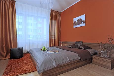 Příjemná paleta barev použitých v ložnici je doplněná potištěným plátnem s motivem kamenů