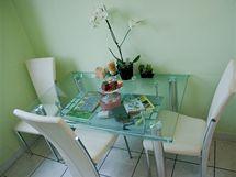 U okna stál skleněný jídelní stůl a tři čalouněné židle