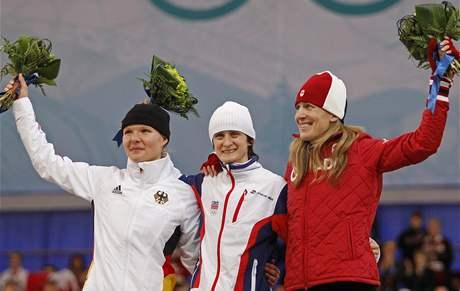 Květinový ceremoniál s medailistkami ze závodu rychlobruslařek na 3000 metrů.