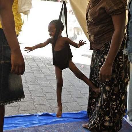 Matka sleduje, jak sestra Frederick Marjorine váží její podvyživené dítě, zavěšené ve vážících kalhotkách ve stanu centra přátelského dětem na Champs-de-Mars Plaza in Port-au-Prince.