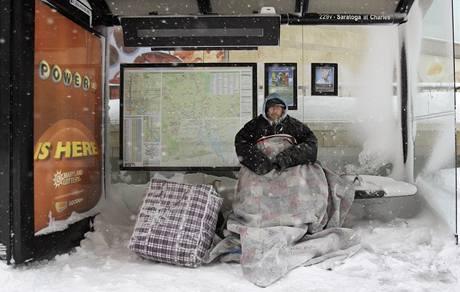 Victor Calderon se schovává před sněhovou bouří na zastávce MHD v Baltiomoru.