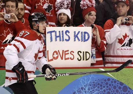 """SID. Kanaďan Sidney Crosby před zápasem se Švýcarskem. V pozadí transparent: """"Tohle dítě miluje Sida."""""""
