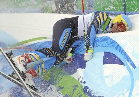 TVRDÝ DOJEZD. Švéd Patrik Jaerbyn naráží do ochranné bariéry v cíli závodu sjezdařů.