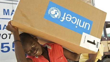 Chlapec přenáší krabici s pomůckami UNICEF, vyloženými z kamionu v dětském centru Don Bosco v Port-au-Prince, jednom z bezpečných míst pro děti, zřízených a podporovaných UNICEF.