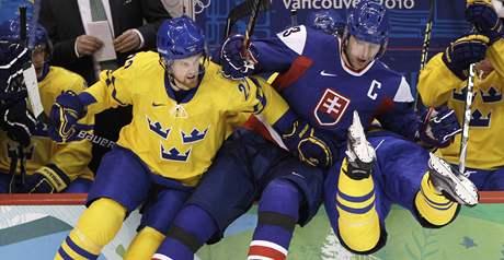 Daniel Sedin (vlevo) a Zdeno Chára se posadili na mantinel u švédské střídačky. Přes něj přepadl Henrik Tallinder.