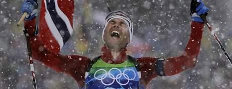 DALŠÍ ZLATO PRO LEGENDU. Finišman norské štafety biatlonistů, Ole Einar Björndalen, se s vlajkou v ruce raduje z vítězství. Získal tak již své šesté olympijské zlato.