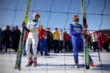 Předskokani sledují olympijský závod družstev ve skoku na lyžích.