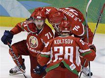 Běloruský hokejista Kaljužnyj (vlevo) příjímá gratulace spoluhráčů Koltsova (zády) a Kosticyna.