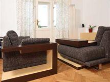 V obývací místnosti jsou dvě pohovky. Ke každé patří jeden atypický stolek, který slouží jako odkládací plocha. V případě potřeby je možné oba stolky spojit v jeden